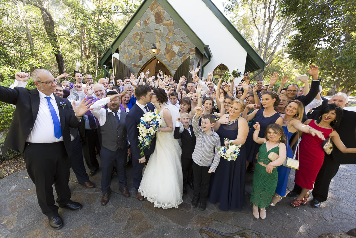 Bride and Groom kiss while their guests cheer